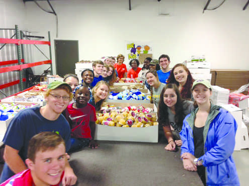 Students in University Life 100 volunteer at Help4Kids warehouse packing food for hungry children as a part of the course requirements.