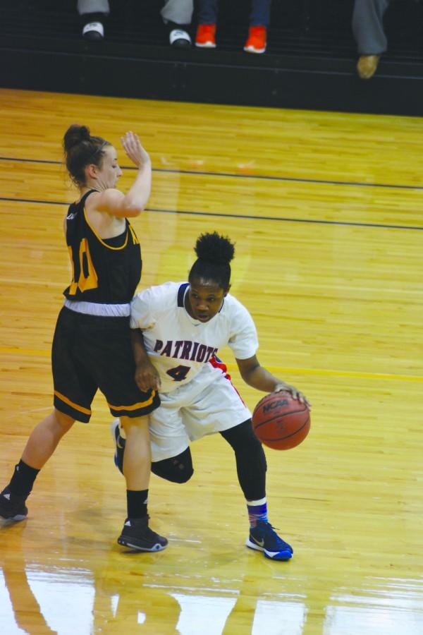 Camille Dash (4) moves the ball up the court towards the basket against Pirate defenders.