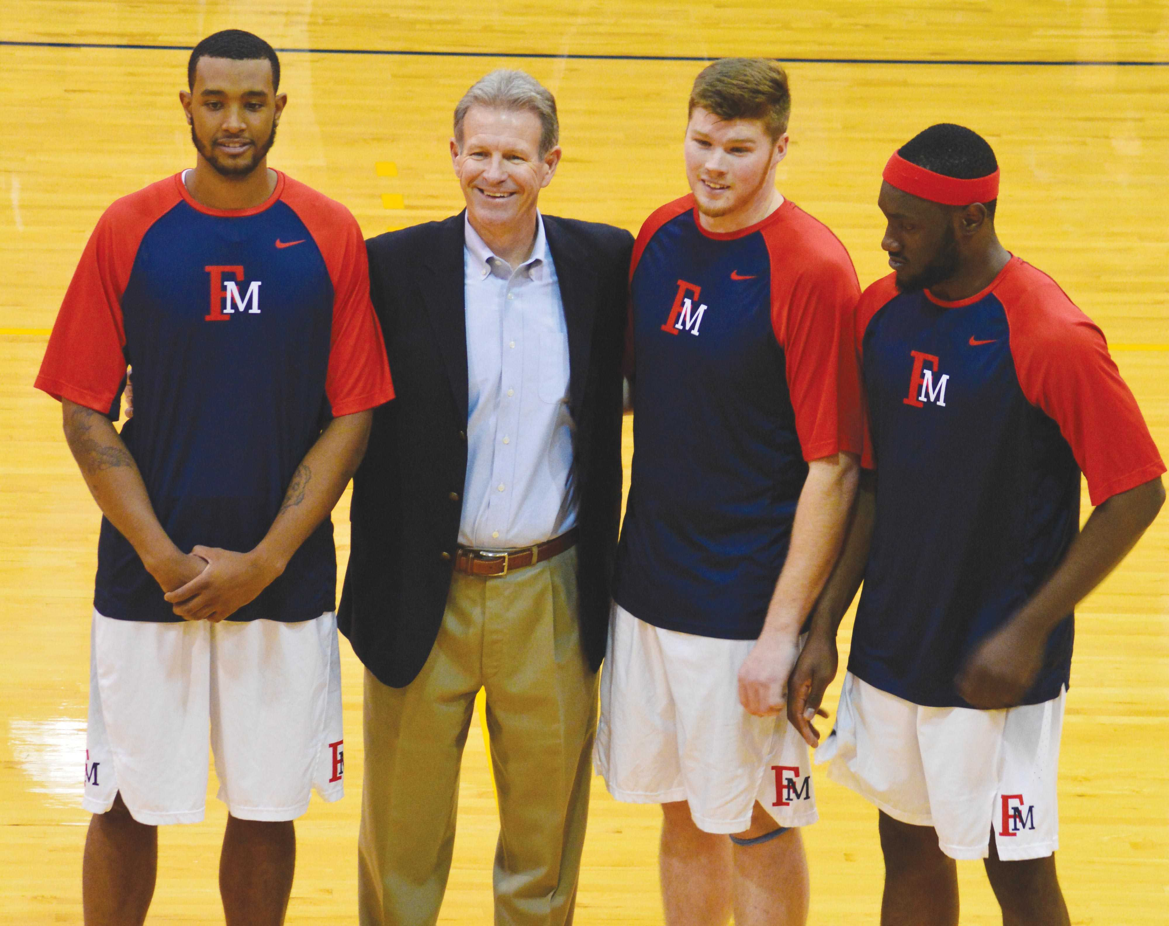 Head coach, Gary Edwards, poses with seniors Nigel Holley (42), Kenneth Jackson (40) and Samson Nnaji (5) before the last home game of the season.