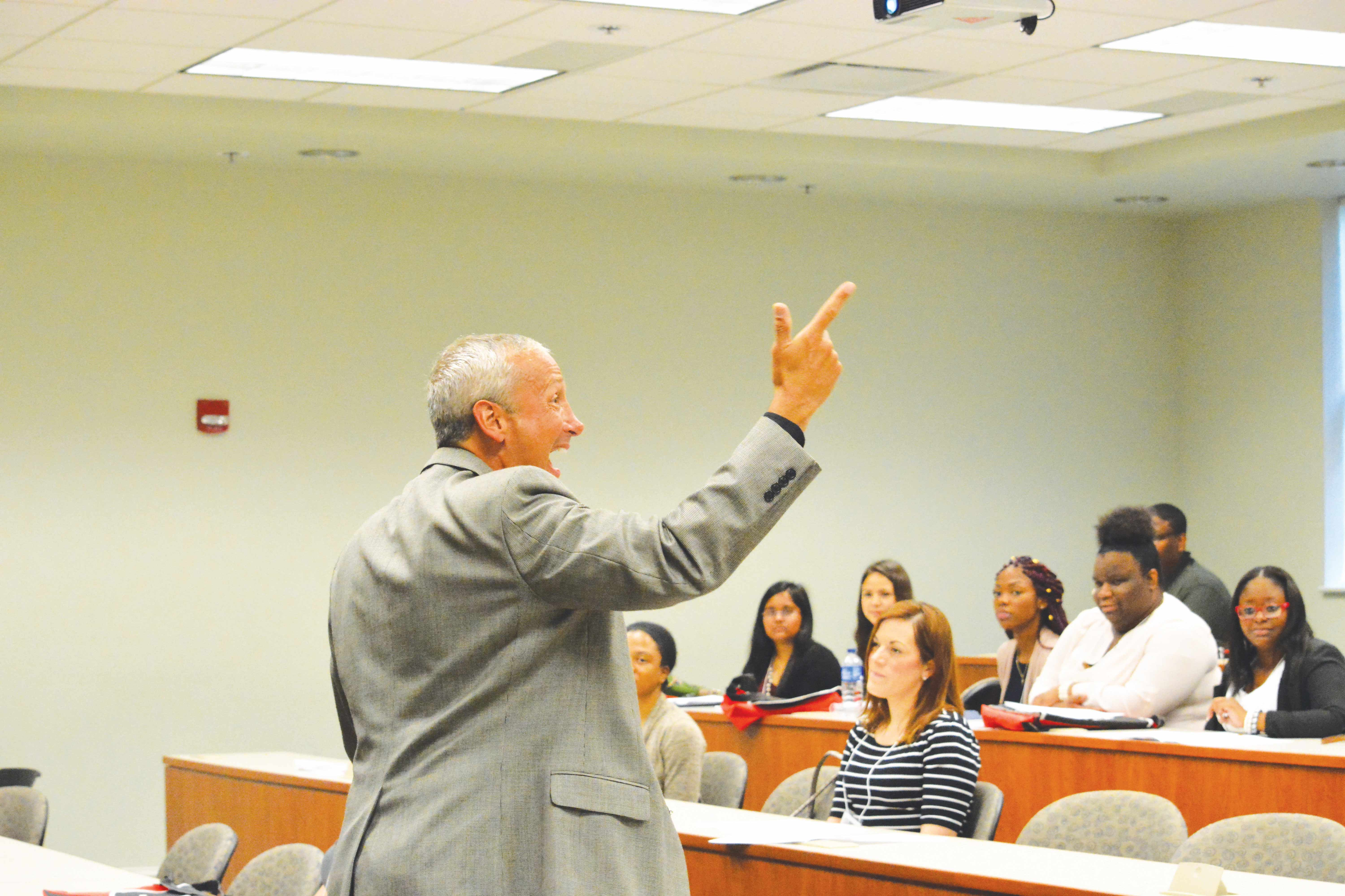 Dr. Hubert Seltzer, a business professor, speaks to students about the value of good communication skills to a leadership.