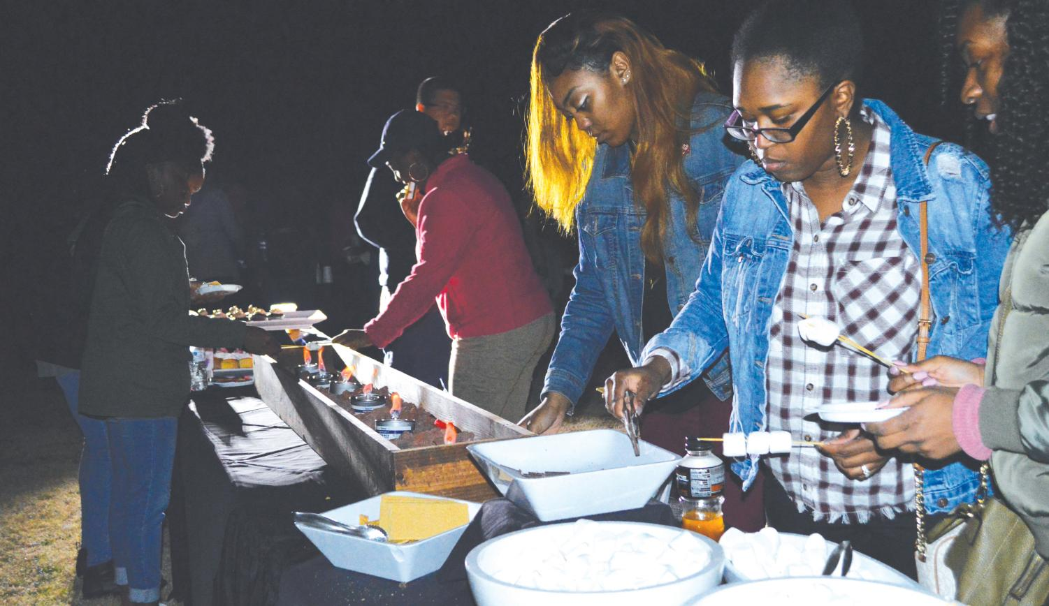 Students gather around the dessert bar to build their s'mores and eat sweet treats while waiting for the bonfire to be lit.