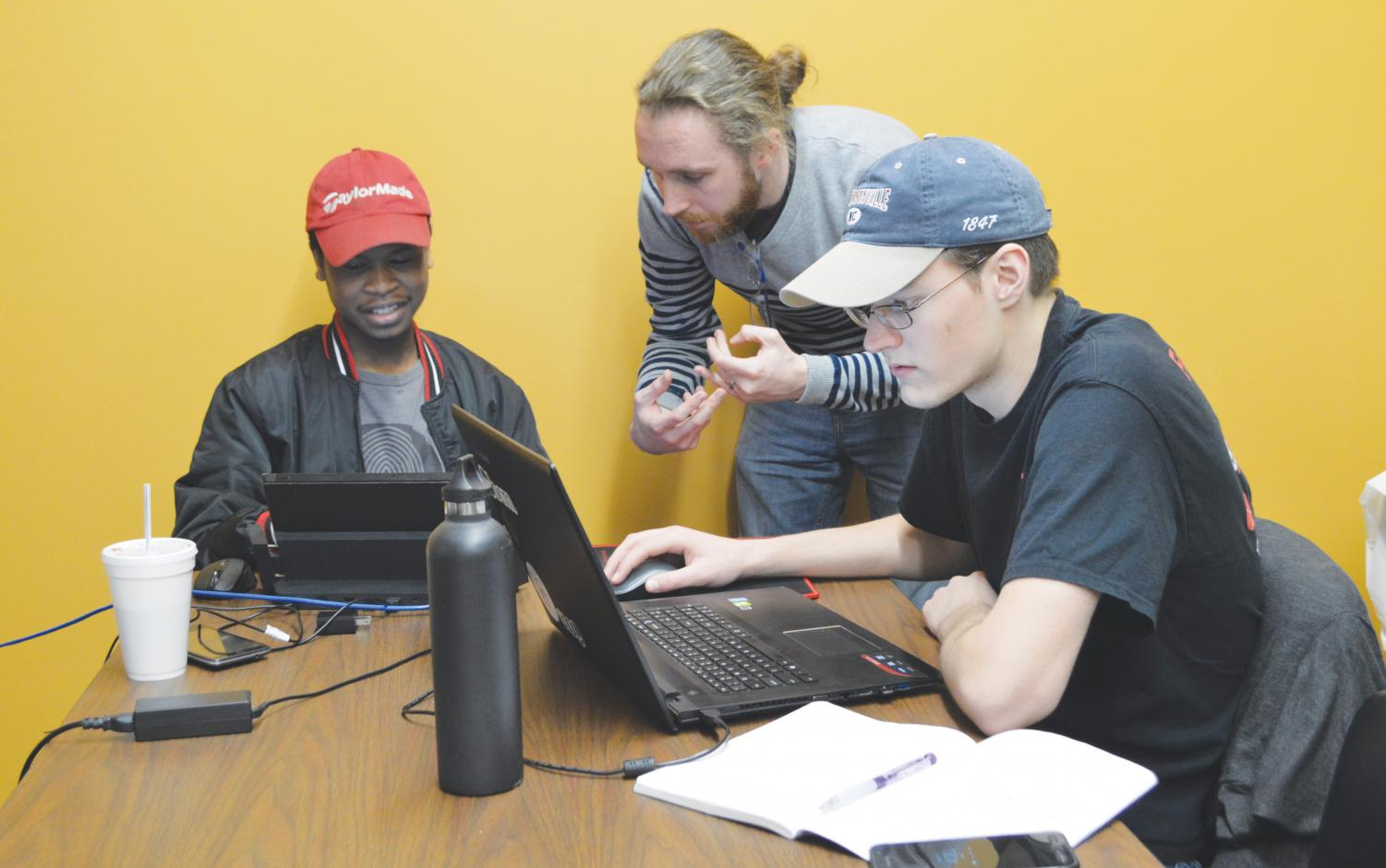 "FMU students James McCarley and Laurence Martin work with programmer Bryant Ward on the ""Whose Lips"" game at the Kelley Center for Enterprise and Innovation."