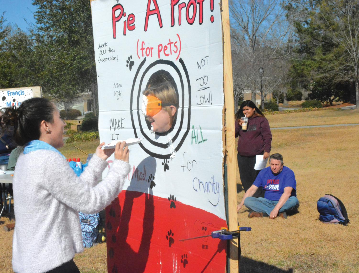 Student Elizabeth Floyd throws a pie at a professor to help raise money and awareness for the Marion county Humane Society.