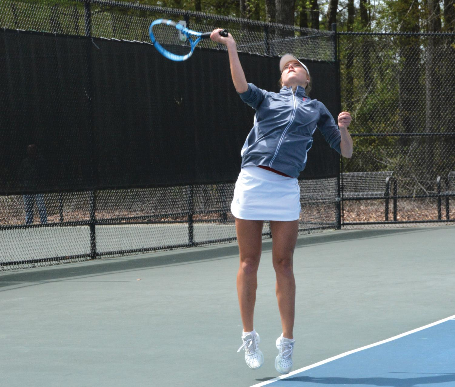 Senior Sofia Henning serves the tennis match during her last singles match as a lady Patriot.