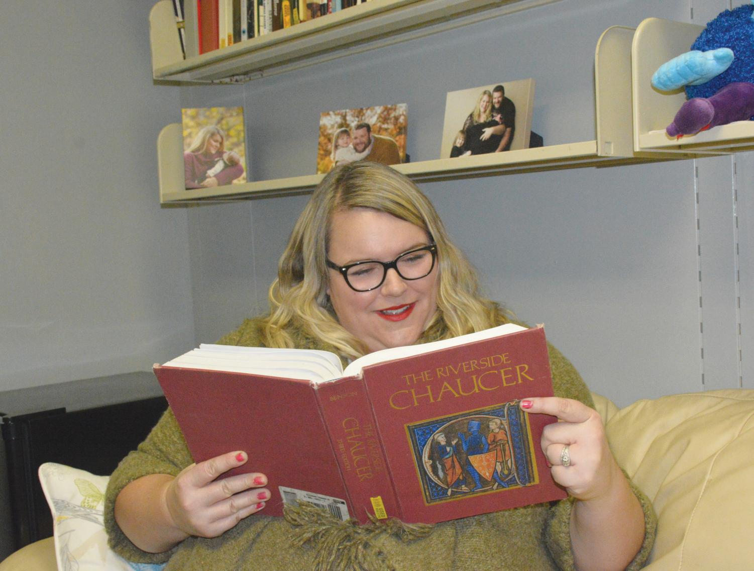 Assistant professor of English Megan Woosley-Goodman, who enjoys old English, sits and read her favorite book.