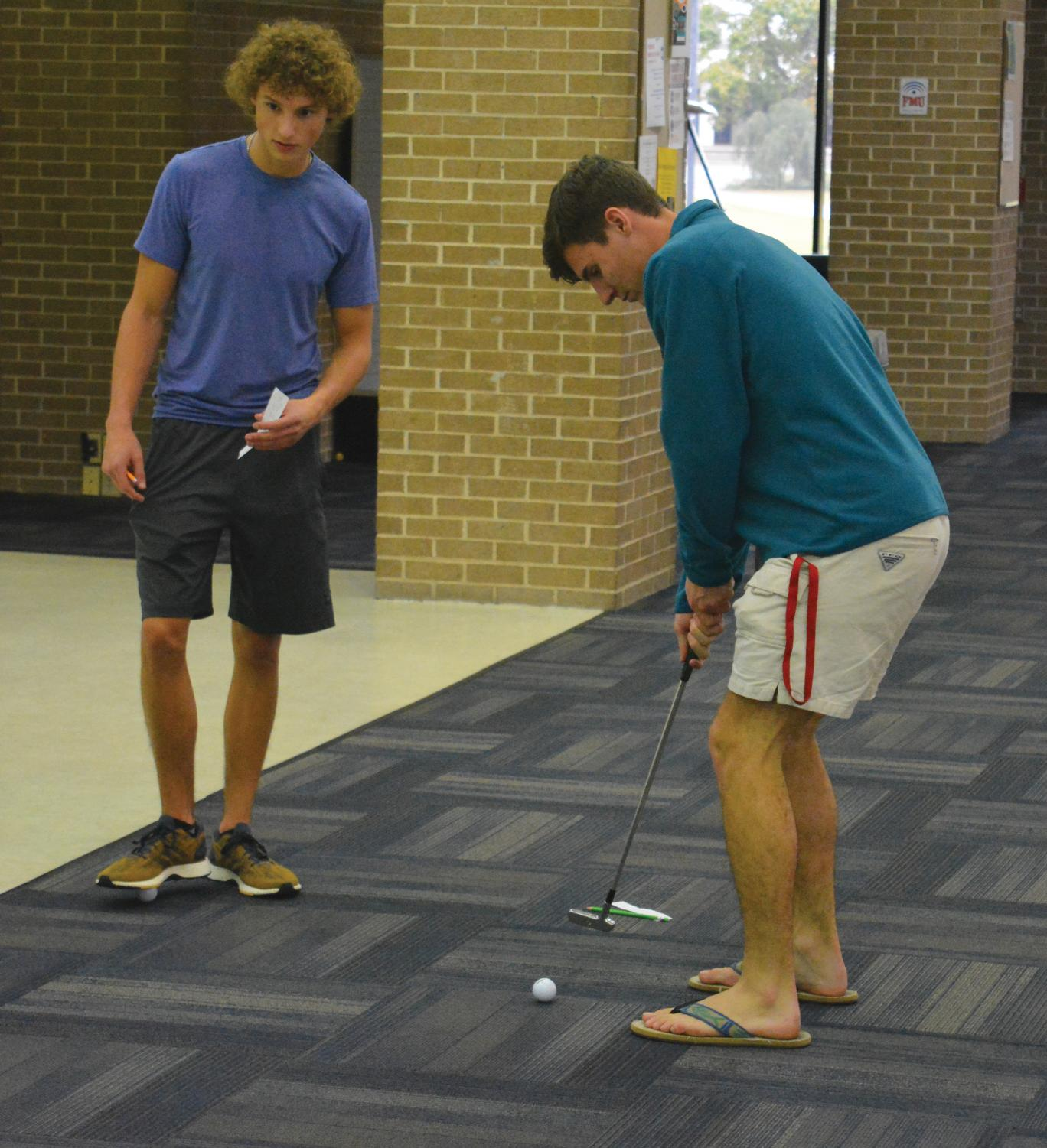 Two students compete in the ultimate putt-putt tournament.