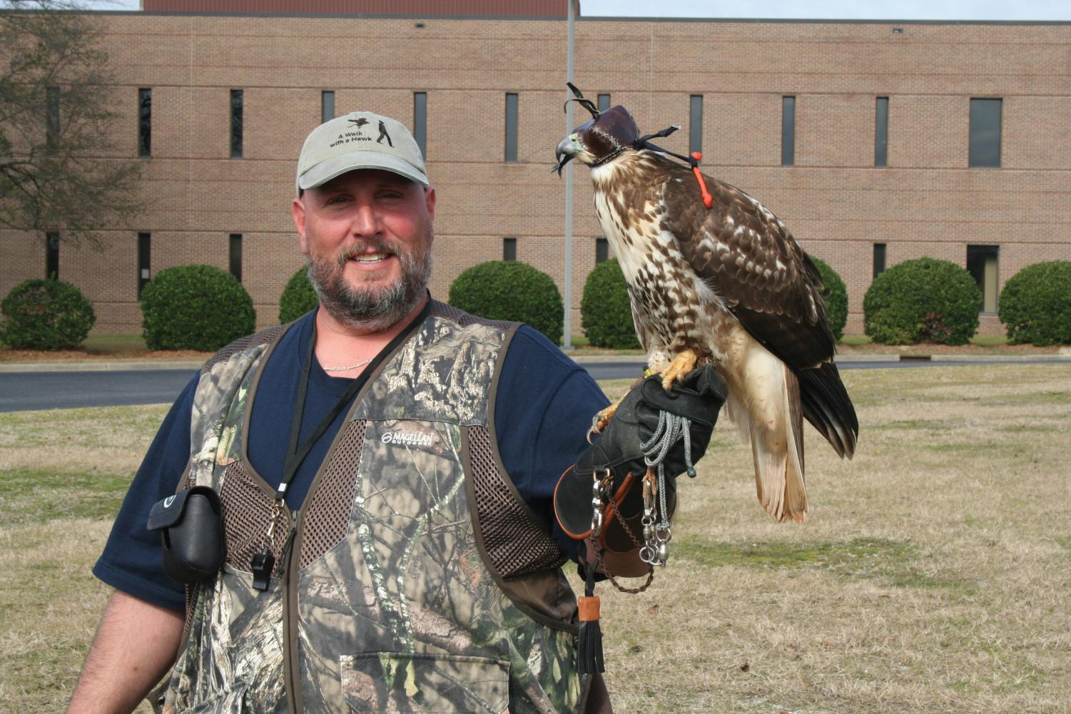 Joel King poses with his juvenile red-tailed hawk, Stella.