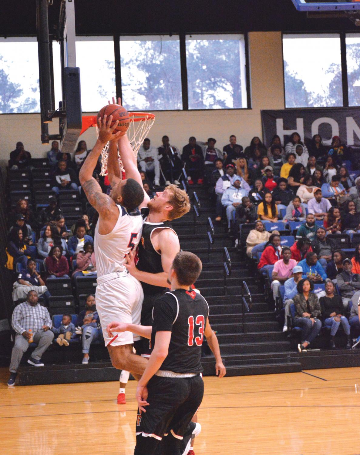 Ryan Davis attempts to dunk on Flagler players.