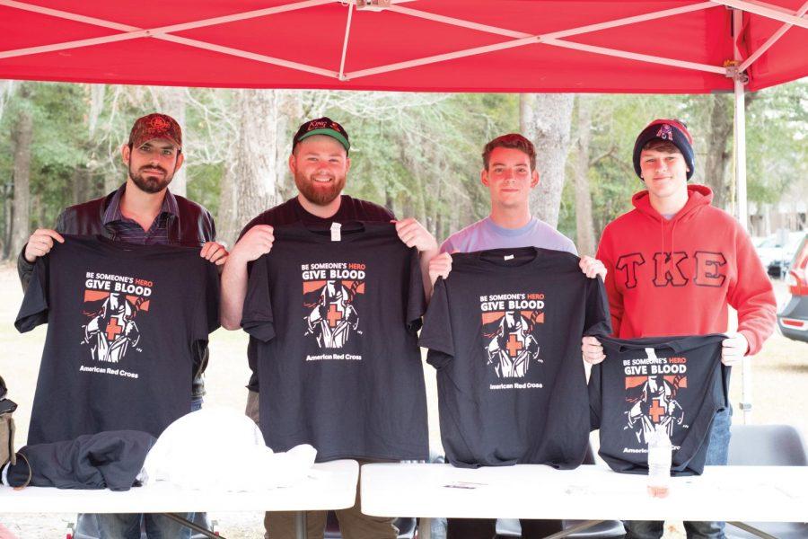 Trey Czarnopys, Matthew Mendelsohn and Joshua Chandler display Red Cross T-shirts.