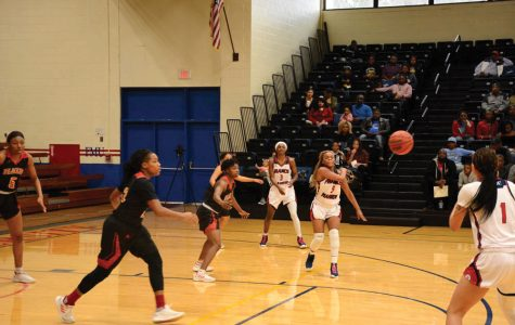 Abigail Bullock passes the ball to Kiana Adderton.