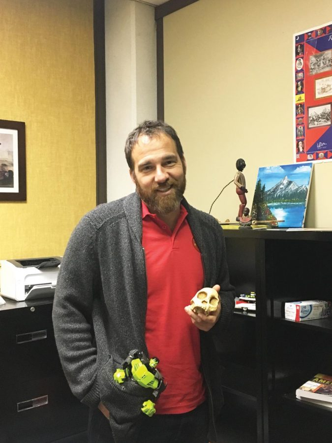 Assistant Professor of Archeology Christopher Barton poses with a skull and action figure.