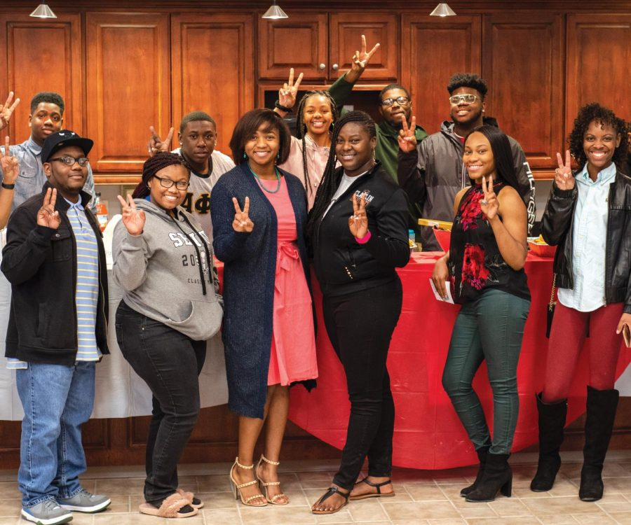 Tylic Galloway poses with students after hosting a event to be in the running for Alpha Kappa Alphas Miss Black and Gold Pageant.