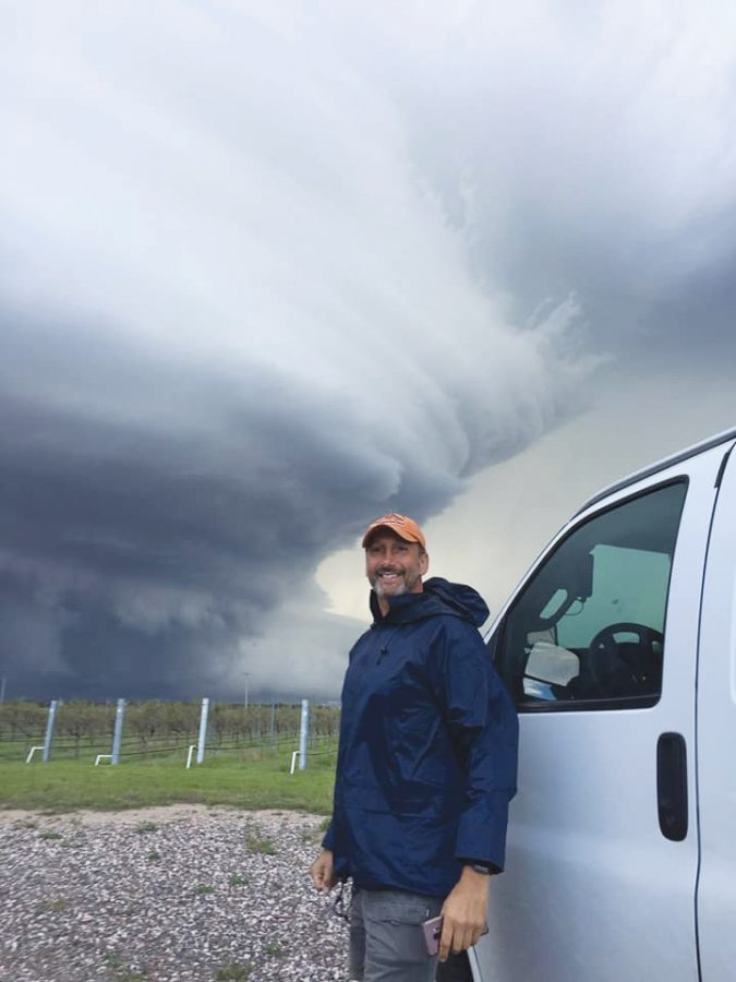 Setzler+poses+in+front+of+a+tornado.+
