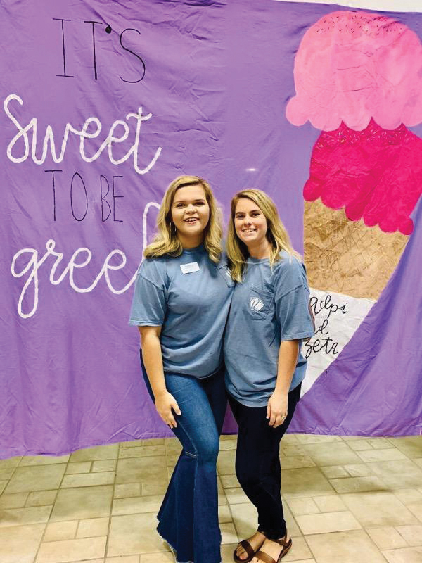 Tindall Hutchinson and Meredith Murphy pose with the its sweet to be greek banner.