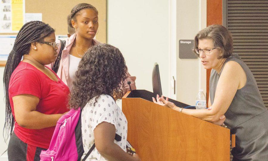 Deborah Potter speaks with FMU students after her presentation.