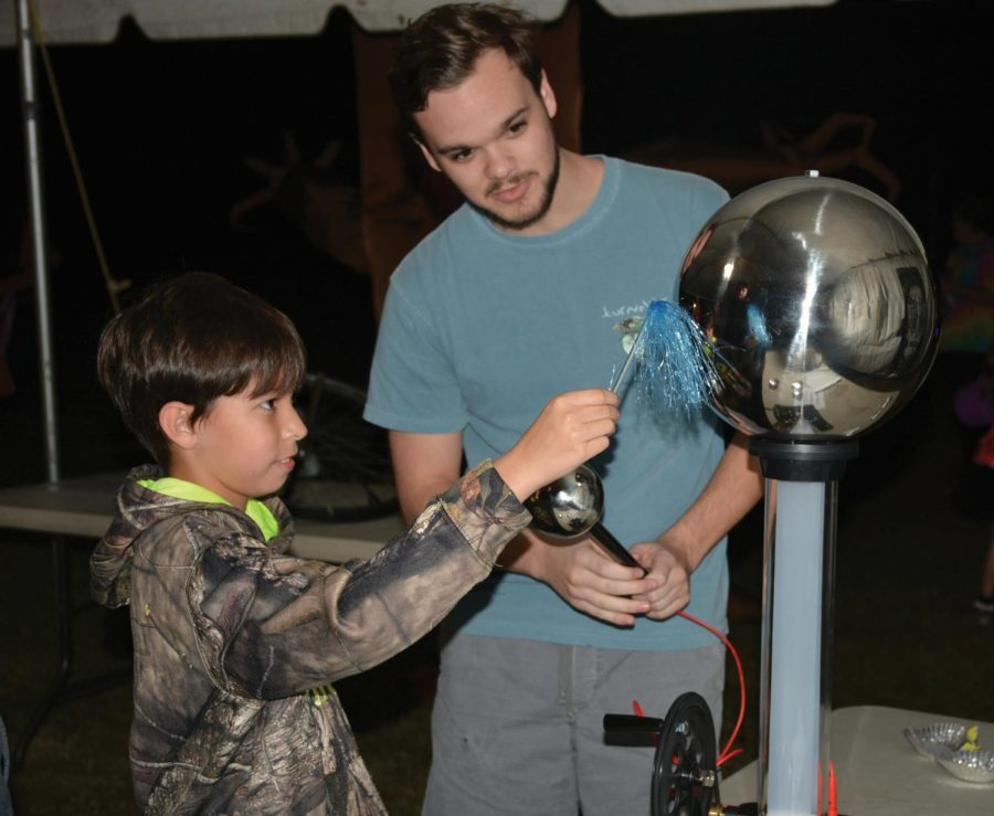 Dylan Hall demonstrates his physics skills for a child at Trick or Treat with Telescopes.