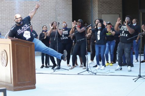"Jeffrey Lampkin leads YGB in a gospel song during the ""Our Voices as One"" event outside the Smith University Center."