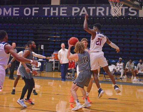 Darius Dawson #21 tries to block an attempted shot from Braves #14 in a hotly contested game.