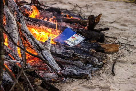 Students burn journals, calendars and other mementos from 2020 in a bonfire outside the UC.