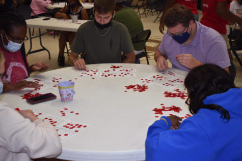 Students fill their bingo cards with circular chips after the latest number is called.